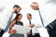 Бизнесмены в офисе имея переговор и используя цифровую таблетку Стоковое Изображение