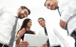 Бизнесмены в офисе имея переговор и используя цифровую таблетку Стоковое фото RF
