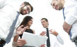 Бизнесмены в офисе имея переговор и используя цифровую таблетку Стоковые Изображения