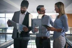 Бизнесмены в офисе имея переговор и используя technolo Стоковая Фотография