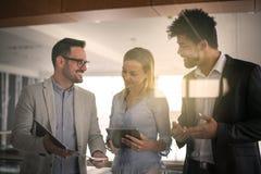 Бизнесмены в офисе имея переговор и используя technolo Стоковые Изображения RF