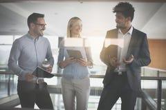 Бизнесмены в офисе имея переговор и используя technolo Стоковое Изображение RF