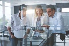 Бизнесмены в офисе имея переговор и используя technolo Стоковые Изображения
