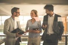 Бизнесмены в офисе имея переговор и используя technolo Стоковое Фото