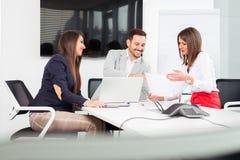 Бизнесмены в офисе проводя конференцию и обсуждая стратегии Стоковые Фото