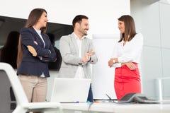 Бизнесмены в офисе проводя конференцию и обсуждая стратегии Стоковые Изображения