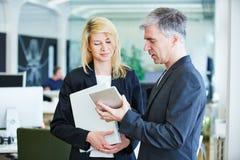 Бизнесмены в офисе с планшетом Стоковые Изображения RF