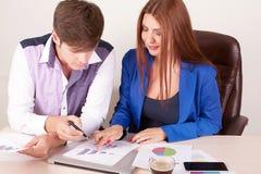2 бизнесмены в элегантных костюмах сидя на столе работая в команде вместе с документами подписывают вверх контракт, держа доску с Стоковые Изображения RF