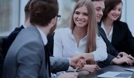 Бизнесмены в formalwear сидя на таблице Стоковые Изображения RF