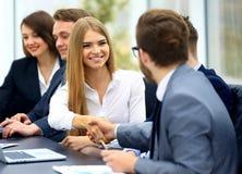 Бизнесмены в formalwear сидя на таблице Стоковые Изображения