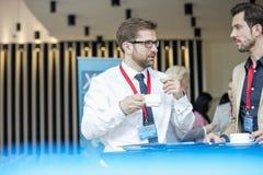 Бизнесмены говоря во время перерыва на чашку кофе на лобби выставочного центра Стоковые Фотографии RF