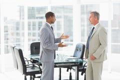 Бизнесмены говоря в конференц-зале Стоковые Изображения RF