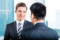 Бизнесмены говоря в обсуждать офиса Стоковая Фотография