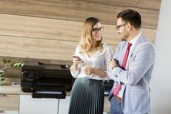 Бизнесмены говоря в офисе mashine блока развертки Стоковая Фотография