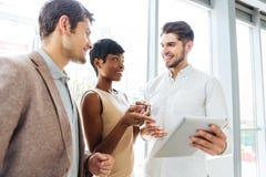 Бизнесмены говоря и используя таблетку совместно в офисе Стоковые Изображения
