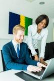 Бизнесмены говоря и усмехаясь в офисе перед l Стоковое Изображение RF