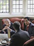 Бизнесмены говоря над компьтер-книжкой в лобби Стоковое Изображение RF