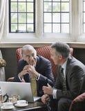 Бизнесмены говоря над компьтер-книжкой в лобби Стоковое фото RF