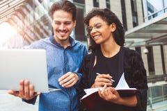 Бизнесмены говоря на улице используя компьтер-книжку стоковая фотография rf