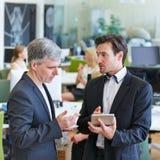Бизнесмены говоря о планшете Стоковое Фото