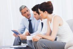Бизнесмены говоря о файлах на софе Стоковое Изображение RF