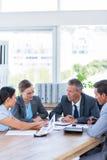 Бизнесмены говоря совместно во время встречи Стоковая Фотография RF