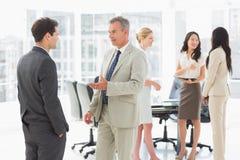Бизнесмены говоря совместно в конференц-зале Стоковые Фото