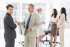 Бизнесмены говоря совместно в конференц-зале Стоковая Фотография RF