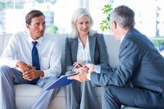 Бизнесмены говоря совместно на кресле Стоковая Фотография