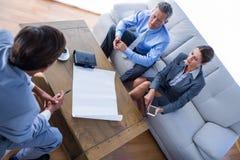 Бизнесмены говоря совместно на кресле Стоковое Фото