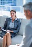 Бизнесмены говоря совместно на кресле Стоковые Изображения
