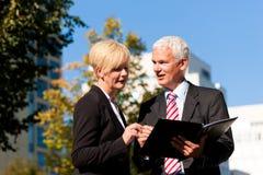 Бизнесмены говоря outdoors Стоковое Фото