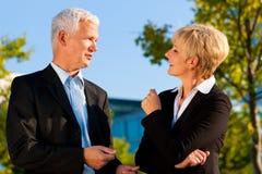 Бизнесмены говоря outdoors Стоковые Фото