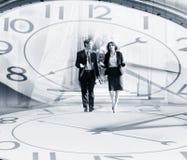 Бизнесмены гуляя на предпосылку часов Стоковая Фотография RF