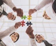Бизнесмены держа и кладя части головоломки стоковое изображение rf