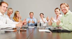 Бизнесмены держа большие пальцы руки вверх в встрече Стоковое Изображение