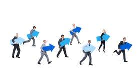 Бизнесмены держа голубые знаки стрелки Стоковая Фотография