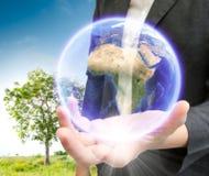 Бизнесмены держа землю Стоковые Фото
