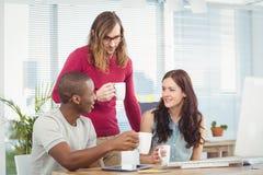 Бизнесмены держа кофейные чашки пока работающ на столе компьютера Стоковое фото RF