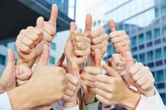 Бизнесмены держа много больших пальцев руки вверх Стоковое Фото