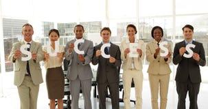 Бизнесмены держа письма говоря успех по буквам акции видеоматериалы