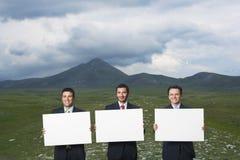 Бизнесмены держа пробел подписывают внутри поле Стоковые Изображения