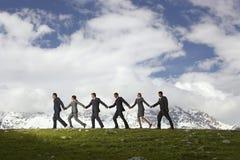 Бизнесмены держа руки и идя через горы Стоковое Фото