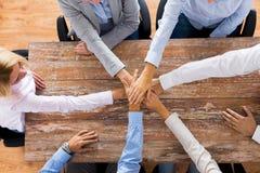 Бизнесмены держа руки на таблице офиса Стоковая Фотография