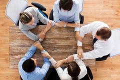 Бизнесмены держа руки на таблице офиса Стоковые Фото