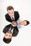 Бизнесмены держа руки совместно изолированный на белизне сыгранность головоломки группы строителей принципиальной схемы дела здан Стоковое Изображение