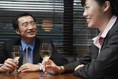 Бизнесмены держа рюмки на таблице кафа Стоковые Изображения