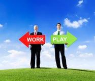 Бизнесмены держа стрелки для работы и игры Стоковое фото RF