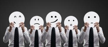 Бизнесмены держа smilies Стоковые Фотографии RF