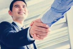 Бизнесмены делая рукопожатие с усмехаясь стороной Стоковые Фото